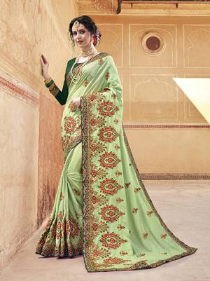 Here Is A Heavy Designer Saree In Light Green Color Paired With Dark Green Colored blouse. This Saree Ans Blouse Are Silk Based Beautified With Heavy Embroidery With Contrasting Thread Work Making It More Attractive.