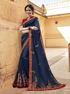 Enhance Your Personality Wearing This Designer Saree In Navy Blue Color Paired With Contrasting Red Colored Blouse, This Saree And Blouse Are Fabricated On Art Silk Beautified With Contrasting Embroidery Giving It An Attractive Look.