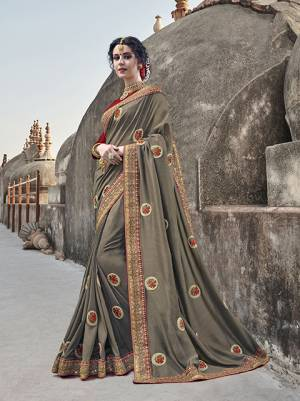 Flaunt Your Rich And Elegant Taste Wearing This Designer Saree In Dark Grey Color Paired With Contrasting Red Colored Blouse. This Saree Is Fabricated On Silk Georgette Paired With Art Silk Blouse. Its Rich Color And Fabric Will Earn You Lots Of Compliments From Onlookers.