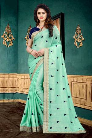 Very Pretty Shade In Here With This Designer Saree In Turquoise Blue Color Paired With Navy Blue Colored Blouse. This Saree Is Fabricated On Georgette Paired With Brocade Fabricated Blouse. It Has Pretty Butti Work All Over It With Embroidered Lace Border.
