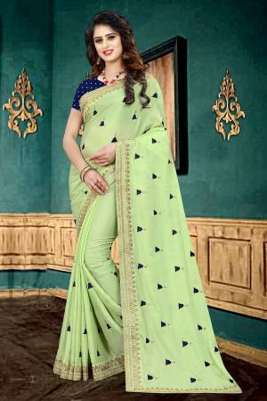 Very Pretty Shade In Here With This Designer Saree In Light Green Color Paired With Navy Blue Colored Blouse. This Saree Is Fabricated On Georgette Paired With Brocade Fabricated Blouse. It Has Pretty Butti Work All Over It With Embroidered Lace Border.