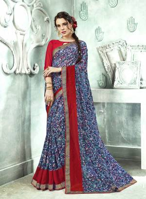 Bright And Appealing Color Is Here With This Saree In Blue Color Paired With Red Colored Blouse. This Saree And Blouse are Georgette Based Beautified With Prints And Lace Border. Its Fabrics Ensures Superb Comfort All Day Long.