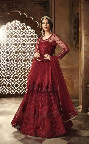 For A Royal Look, Grab This Heavy Designer Floor Length Suit With Double Layered Pattern. Its Rich Maroon Color Will Give A Royal Look To Your Personality. Its Top And Dupatta Are Net Based Paired With Santoon Bottom Also Which IS Having A Satin Inner With Can Can Attached. Its Top Is Beautified With Heavy Resham Embroidery And Moti Hand Work. Buy Now.