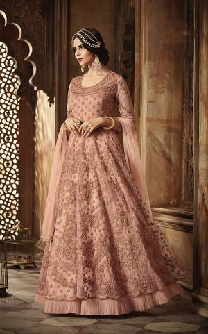 Look Pretty Wearing This Designer Floor Length Suit In Very Pretty Dusty Pink Color. Its Pretty Color Will Definitely Earn You Lots Of Compliments From Onlookers. Its Top And Dupatta Are Net Based Paired With Santoon Bottom.