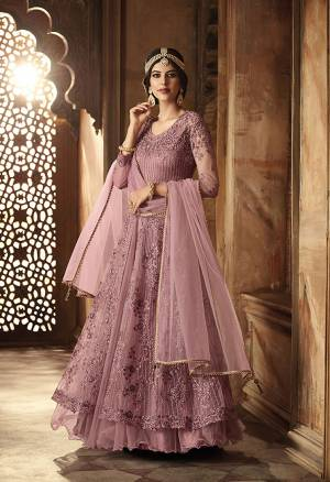 New Shade Is Here To Add Into Your Wardrobe For The Upcoming Wedding Season. Grab This Designer Floor Length Suit In Mauve Color. Its Top And Dupatta Are Net fabricated Paired With Santoon Bottom. Also It Has Satin Inner With Can Can Attacthed. Buy Now.