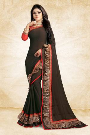 Celebrate This Festive Season With Beauty And Comfort Wearing This Designer Saree In Dark Brown Color Paired With Contrasting Red Colored Blouse. This Saree Is Fabricated On Georgette Paired With Art Silk Fabricated Blouse. It Has Fancy Lace Border Giving It An Attractive Look.
