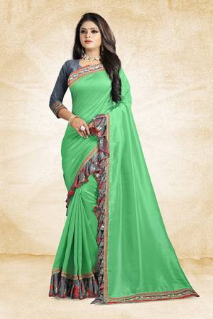Look Pretty Wearing This Designer Silk Based Saree In Green Color Paired With Grey Colored Blouse. This Saree And Blouse Are Silk Based Beautified With Lace Border And Printed Frill Over The Border. Buy This Pretty Saree Now.