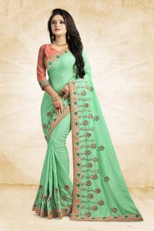 Look Pretty In This Lovely Designer Saree In Light Green Color Paired With Peach Colored Blouse. This Pretty Embroidered Saree In Fabricated On Satin Silk Paired With Art Silk Fabricated Blouse. It Has Contrasting Colored Embroidery Giving The Saree An Attractive Look.