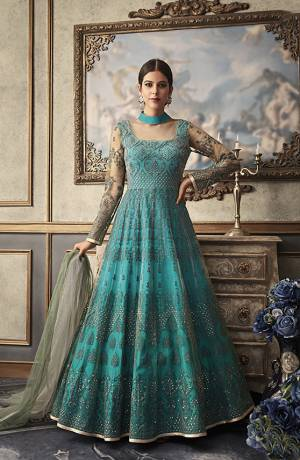 You Will Earn Lots Of Compliments Wearing This Heavy Designer Floor Length Suit In Turquoise Blue Color Paired With Contrasting Grey Colored Dupatta. Its Top And Dupatta Are Net Based Beautified With Heavy Embroidery Paired With Art Silk Fabricated Bottom And Inner.