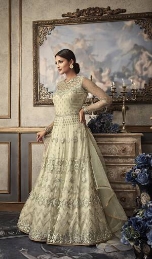 Simple And Elegant Looking Heavy Designer Floor Length Suit Is Here In Off-White Color Paired With Off-White Colored Bottom And Dupatta. Its Heavy Embroidered Top Is Fabricated On Net Paired With Art Silk Bottom And Net Fabricated Dupatta. Buy This Designer Suit Now.