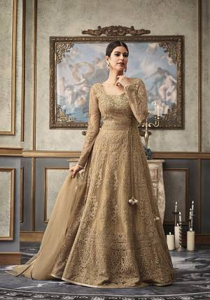 Flaunt Your Rich And Elegant Taste Wearing This Heavy Designer Floor Length Suit In Beige Color Paired With Beige Colored Bottom And Dupatta. Its Heavy Embroidered Top Is Net Based Paired With Art Silk Bottom and Net Fabricated Dupatta. Buy This Rich Designer Suit Now.