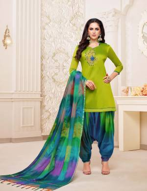 Rich And Elegant Looking Patiala Suit In Parrot Green Colored Top Paired With Blue Colored Bottom And Dupatta. This Dress Material Is Fabricated On Soft Silk Beautified With Hand Work Over The Top. Buy Now.