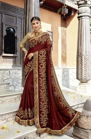 For A Royal Look, Grab This Heavy Designer Saree In Maroon Color Paired With Golden Colored Blouse. This Saree And Blouse Are Silk Based With Attractive Embroidery. Its Royal Color Pallete And Rich Fabric Will Earn You Lots Of Compliments From Onlookers.