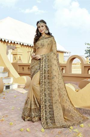 Flaunt Your Rich And Elegant Taste Wearing This Designer Saree In Beige Color Paired With Golden Colored Blouse. This Saree Is Fabricated On Orgenza Paired With Art Silk Fabricated Blouse. It Has Heavy Embroidery Which Earns You Lots Of Compliments From Onlookers.