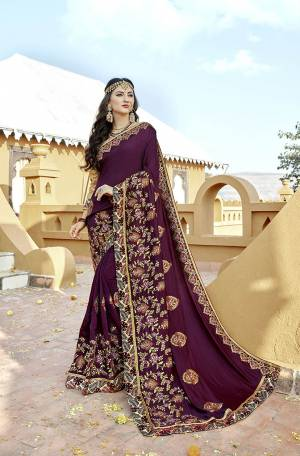 A Must Have Shade In Every Womens Wardrobe Is Here With This Designer Saree In Wine Color Paired With Golden Colored Blouse. This Saree And Blouse Are Silk Based Beautified With Embroidery All Over.