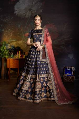 Enhance Your Personality Wearing This Heavy Designer Lehenga Choli In Navy Blue Color Paired With Contrasting Pink Colored Dupatta. This Heavy Embroidered Lehenga Choli Is Fabricated On Satin Paired With Net Dupatta. Its Fabrics Are Soft Towards Skin And Easy To Carry All Day Long.