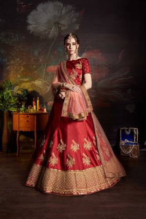 Get Ready For The Upcoming Wedding Season With This Designer Heavy Lehenga Choli In Red color Paired With Peach Colored Dupatta. Its Blouse And Lehenga Are Fabricated On Satin Paired With Net Fabricated Dupatta. It Has Pretty Attractive Embroidery All Over It.