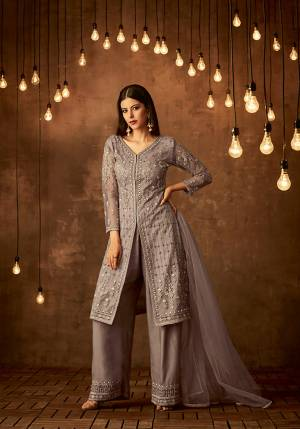 New Shade Is Here To Add Into Your Wardrobe With This Designer Suit In Mauve Grey Color Which Is Shade Of Light Purple And Grey. Its Top And Dupatta Are Net Fabricated Paired With Satin Raw Silk Fabricated Bottom. It Has Very Pretty Tone To Tone Embroidery Which Is Giving A Pretty Subtle Look.
