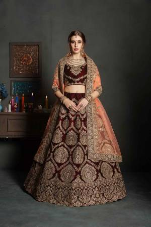 Here Is A Perfect Bridal Look For You In The Running Treand With This Heavy designer Lehenga Choli In Maroon Color Paired With Contrasting Peach Colored Dupatta. This Lehenga Choli Is Velvet Based Paired With Net Fabricated Dupatta.Its Fabric Also Ensures Superb Comfort Throughout The Gala
