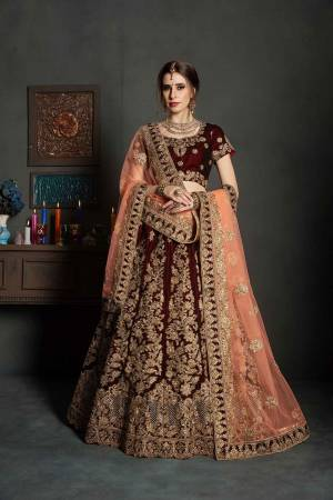 Get Ready For Your Big Day With This Latest Bridal Trend, Wearing This Heavy Designer Lehenga Choli In Maroon Color Paired With Contrasting Peach Colored Dupatta. This Heavy Embroidered Lehenga Choli Is Fabricated On Velvet Paired With Net Fabricated Dupatta. It Is Beautified With Heavy Embroidery and Stone Work. Buy Now