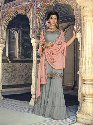 For A Rich And Elegant Look For You And Your Daughter Here Is A Perfect Sharara Suit In Grey Colored Top And Bottom Paired With Contrasting Peach Colored Dupatta. Its Top And Bottom Are Fabricated On Georgette Paired With Chiffon Dupatta. Buy Now.