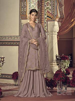 Here Is A Very Beautiful Shade In Purple With This Designer Sharara Suit In Mauve Color For You And Your Daughter. This Pretty Suit Is Georgette Based Paired With Net Fabricated Dupatta. It Is Beautified With Attractive Embroidery Over The Top And Dupatta. Buy Now.
