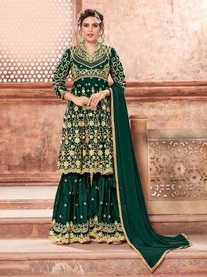 This Festive Season, Grab This Heavy Designer Sharara Suit In Dark Green Color Paired With Dark Green Colored Bottom And Dupatta. Its Heavy Embroidered Top And Bottom Are Fabricated On Satin Georgette Paired With Chinon Fabricated Dupatta. Buy This Semi-Stitched Suit Now.