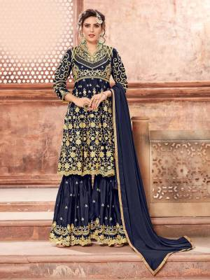 This Festive Season, Grab This Heavy Designer Sharara Suit In Navy Blue Color Paired With Navy Blue Colored Bottom And Dupatta. Its Heavy Embroidered Top And Bottom Are Fabricated On Satin Georgette Paired With Chinon Fabricated Dupatta. Buy This Semi-Stitched Suit Now.