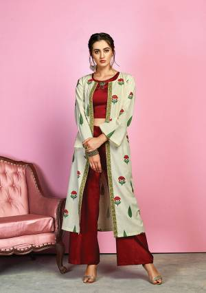 Grab This Designer Indo-Western Dress In Maroon Colored Top And Bottom Paired With Off-White Colored Jacket. Its Crop Top And Pants Are Fabricated On Cotton Satin Paired With Handloom Cotton Floral Printed Jacekt. I