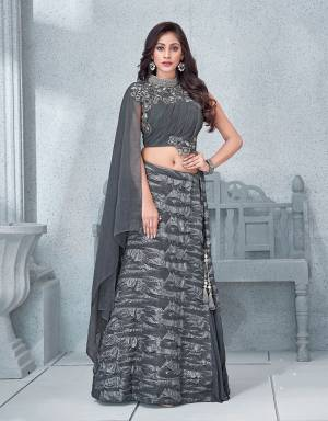 This glittering silver Grey lehenga with an asymetric blouse is as sensual and as charismatic as it gets.  Add statement earrings to it to complete the look.