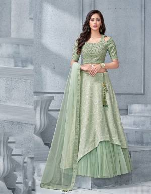 The subtle hued lehenga with an asymmetric cut to it paired with a matching cold-shoulder blouse exudes a crystalline feel to it making it an alluring pick.
