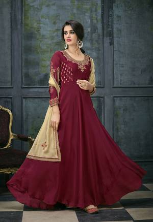 For A Royal Look, Grab This Deisgner Floor Length Suit In Maroon Color Paired With Beige Colored Dupatta. Its Pretty Embroidered Top Is Fabricated On Satin Georgette Paired With Santoon Bottom And Chiffon Dupatta. This Suit Is Light Weight And Easy To Carry All Day Long.