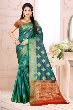 Celebrate This Festive Season Wearing This Saree In Blue Color Paired With Contrsating Orange Colored Blouse. This Saree Is Fabricated On Cotton Silk Paired With Jacquard Silk Fabricated Blouse. It Is Beautified With Weave All Over.