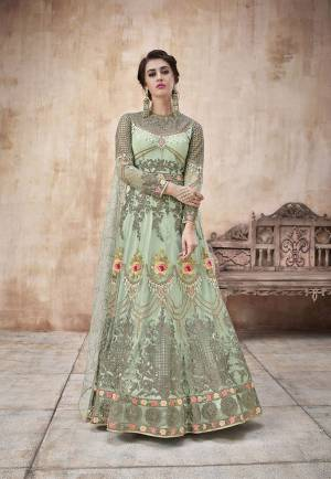 Here Is A Beautiful Designer Floor Length Suit In Light Green Color Paired With Light Green Colored Bottom And Dupatta. Its Heavy Embroidered Top IS Fabricated On Net Paired With Satin Silk Bottom And Net Fabricated Dupatta. This Pretty Suit Earn You Lots Of Compliments From Onlookers.