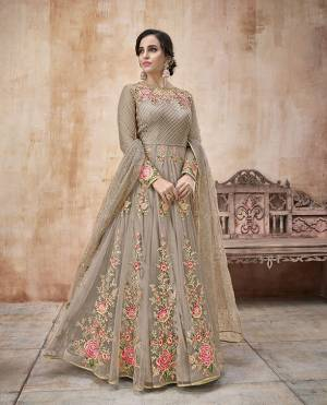 Flaunt Your Rich And Elegant Taste Wearing This Designer Floor Length Suit In Grey Color Paired With Grey Colored Bottom And Dupatta. Its Pretty Embroidered Floor Length Top IS Net Based Paired With Satin Silk Bottom And Net Dupatta.