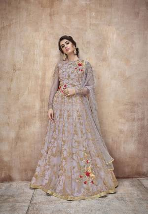 New Shade Is Here To Add Into Your Wardrobe. This Pretty Mauve Colored Designer Floor Length Suit Is A Shade Of Purple And Grey. It Is Paired With Mauve Colored Bottom And Dupatta. Its Heavy Embroidred Top And Dupatta Are Fabricated On Net Paired With Satin Silk Bottom. Buy This Rich Designer Suit Now.