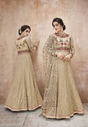 Simple and Elegant Looking Designer Floor length Suit IS Here In Beige Color Paired With Beige Colored Bottom And Dupatta. This Pretty Suit Is Net Based Paired With Satin Silk Fabricated Bottom. Buy This Now.