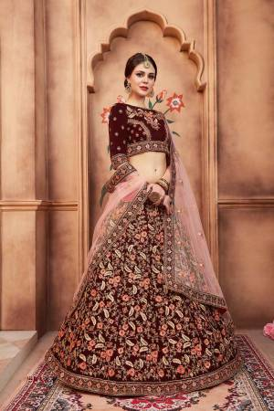 Catch All The Limelight At The Next Wedding You Attend Wearing This Designer Lehenga Choli In Maroon Color Paired With Contrasting Baby Pink Colored Dupatta. Its Blouse And Lehenga Are Fabricated Velvet Paired With Net Fabricated Dupatta.