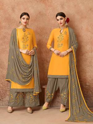 Celebrate This Festive Season With Ease, Comfort And Beauty By Getting This Dress Material Stitched As Per Your Desired Fit And Comfort. Its Top Is In Musturd Yellow Color Paired With Contrasting Grey Colored Bottom And Dupatta. This Dress Material Is Fabricated On Cotton Paired With Chiffon Dupatta.