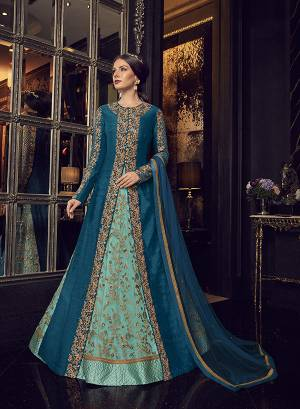 Add This Elegant And New Patterned Indo-Western Dress To Your Wardrobe In Shades Of Blue. It Has Very Pretty Aqua Blue Colored Gown With A Blue Colored Jacket Paired With Aqua Blue Colored Embroidered Pants And Blue Dupatta. Its Heavy Embroidered Gown Is Net Based Paired With Art Silk Jacket , Art Silk Pant And Net Fabricated Dupatta.