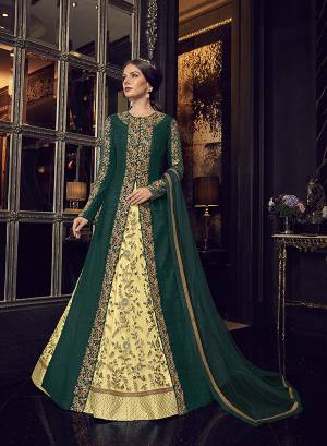 Add This Elegant And New Patterned Indo-Western Dress To Your Wardrobe In Shades Of Green. It Has Very Pretty Light Yellow Colored Gown With A Pine Green Colored Jacket Paired With Light Yellow Colored Embroidered Pants And Pine Green Dupatta. Its Heavy Embroidered Gown Is Net Based Paired With Art Silk Jacket , Art Silk Pant And Net Fabricated Dupatta.