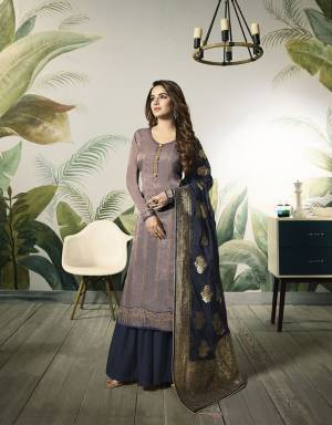 New Color Pallete Is Here To Add Into Your Wardrobe With This Designer Semi-Stitched Suit In Mauve Colored Top Paired With Contrasting Navy Blue Colored Bottom And Dupatta, Its Embroidered Top Is Fabricated On Satin Silk Paired With Santoon Bottom And Banarasi Silk Dupatta.