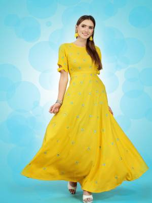 You Will Definitely Earn Lots Of Compliments Wearing This Bright Yellow Colored Long Kurti. This Pretty Kurti Is Fabricated On Rayon Beautified With Thread Work Butti All Over It.