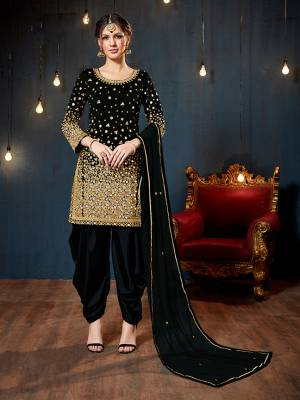 Get Ready For The Upcoming Festive And Wedding Season With This Heavy Designer Suit In Black Color. Its Heavy Embroidered Top Is Fabricated On Tafeta Art Silk Paired With Santoon Bottom And Net Fabricated Dupatta. It Is Beautified With Heavy Jari Embroidery And Mirror Work.