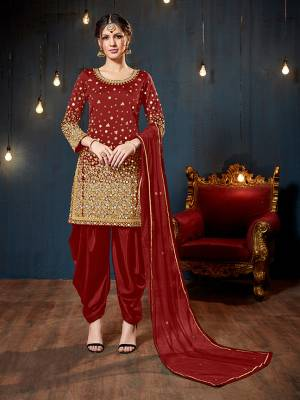 Get Ready For The Upcoming Festive And Wedding Season With This Heavy Designer Suit In Red Color. Its Heavy Embroidered Top Is Fabricated On Tafeta Art Silk Paired With Santoon Bottom And Net Fabricated Dupatta. It Is Beautified With Heavy Jari Embroidery And Mirror Work.