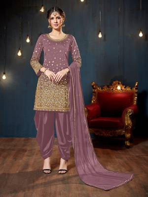 Get Ready For The Upcoming Festive And Wedding Season With This Heavy Designer Suit In Mauve Color. Its Heavy Embroidered Top Is Fabricated On Tafeta Art Silk Paired With Santoon Bottom And Net Fabricated Dupatta. It Is Beautified With Heavy Jari Embroidery And Mirror Work.