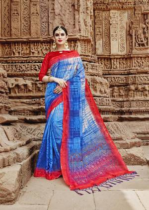 For Your Semi-Casuals. Grab This Beautiful Saree In Blue Color Paired With Contrasting Red Colored Blouse. This Saree And Blouse Are Fabricated On Khadi Silk Beautified Prints. It Is Light In Weight And Easy To Carry All Day Long.