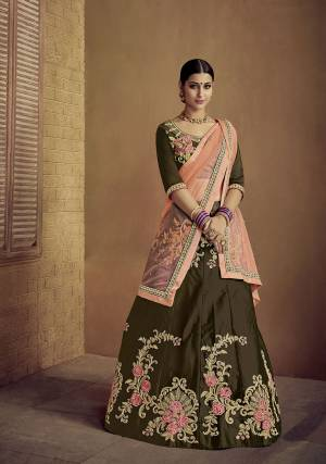 Enhance Your Personality Wearing This Heavy Designer Lehenga Choli In Dark Olive Green Color Paired With Contrasting Peach Colored Dupatta. Its Blouse And Lehenga Are Satin Silk Based Paired With Net Fabricated Dupatta.
