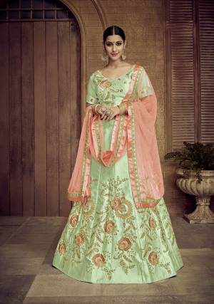Here Is A Proper Traditional Color Pallete With This Heavy Designer Lehenga Choli In Light Green Color Paired With Contrasting Orange Colored Dupatta. Its Blouse And Lehenga Are Satin Silk Based Paired With Net Fabricated Dupatta. Its Fabric Also Ensures Superb Comfort Throughout The Gala.
