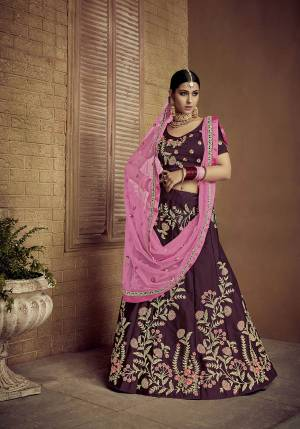 Catch All The Limelight Wearing This Heavy Designer Lehenga Choli In Dark Wine Color Paired With Contrasting Pink Colored Dupatta. Its Blouse And Lehenga Are Satin Silk Fabricated Paired With Net Fabricated Dupatta.
